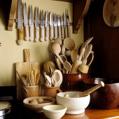 Various cooking utensils made from natural materials such as wooden spoons in ceramic pot and set of knives hanging on the wall
