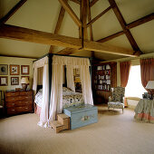 Double bed with canopy in rustic bedroom under vast roof structure