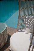 Detail of chair with white seat cushion next to pool