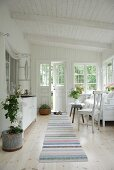 Loggia of white wooden house with white furniture and striped runner on wooden floor