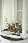 A tray of silver goblets on a white sideboard against a wall with a window