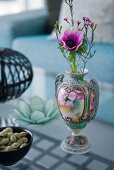A purple flower in a decorative ornamental vase on a glass coffee table