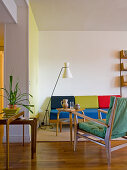 50s living room furnishings with multi-coloured upholstery on light wooden frames, typical standard lamp and various side tables