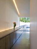 Minimalistischer Wohnraum mit modernem Sideboard unter indirekter Beleuchtung