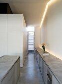 Langes, graues Sideboard mit Kücheneinbaugerät und freistehender Küchenblock im Betonlook