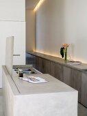 Grauer Küchenblock mit teilweise geöffneter Abdeckplatte und Blick auf Spüle in minimalistischer Designerküche