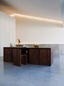 Designer Tisch aus dunklem Holz mit passenden Stühlen in minimalistischem Esszimmer
