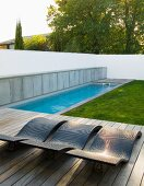 Pool and wooden deck with loungers in garden