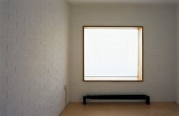 Empty room with white-painted brick wall and window