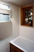 Corner of white-tiled bathroom and bathtub