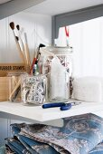 Fabrics, sewing equipment and painting utensils on shelf
