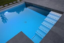 Modern pool with slate-flagged surround and mosaic tiles on steps