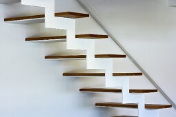 Detail of structure of modern designer staircase with zigzag framework and wooden treads