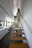 Woman walking down minimalist staircase into open-plan living area with slate floor and large terrace windows