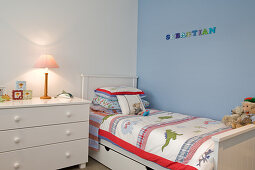 Child's bedroom with white, rustic furniture against blue-painted wall