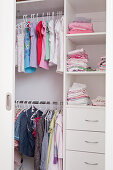 Children's clothing hanging in open-fronted wardrobe with drawers in shelving compartments