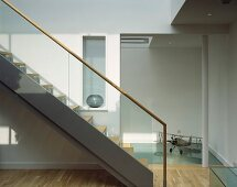 Contemporary staircase in bright stairwell and ceiling-height doorway to hall