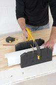 DIY - man standing at workbench sawing