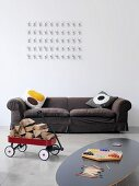 Scatter cushions with graphic patterns on upholstered sofa and artwork on wall with toys in foreground