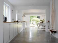Long kitchen unit with model sailing boat on wall and dining area with open terrace door