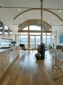 Long kitchen unit and central wood-burning stove in open living space with arched ceiling and view of coastal landscape