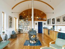 Open-plan, ecological living space with central wood-burning stove and long stovepipe up to arched ceiling