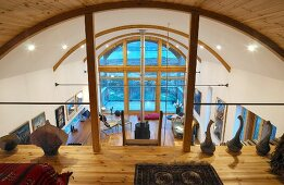 Contemporary wooden building - view of modern living space with arched ceiling from gallery with objets