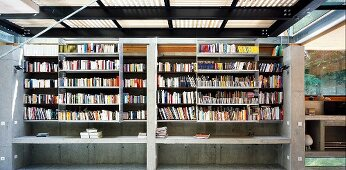 Two-storey concrete bookcase with sliding shelf units at front and gallery level in open steel and wood structure