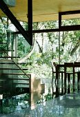 Steel and glass staircase and facade in contemporary solar house with open view of nature