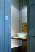 Wood-clad walls, white brick wall and view of glass basin on wooden washstand through open plank door