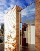 View of open house door through fixed window between wood-clad wall elements