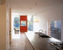 Open-plan kitchen with sink and hob in island and view of red exterior door