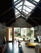 Living space with glass roof structure & view of garden