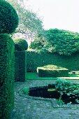Wasserbecken in gepflastertem Bereich einer Gartenanlage mit formgeschnittenen Buxhecken.