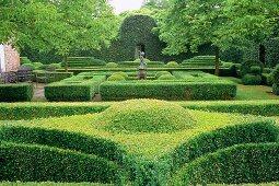 Eindrucksvolle Gartenanlage mit formgeschnittenen Hecken und gestalteten Wegen, ein Beispiel für Gartenarchitektur.