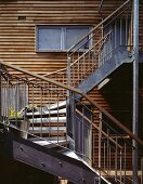 Metal, exterior stairs in front of wooden facade of modern house