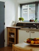 Corner of kitchen with sink and wooden cabinets in front of window