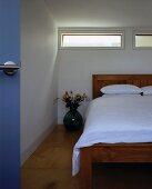 Corner of bedroom with bed beneath narrow window slits