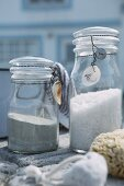 Sand and white gravel in preserving jars with fine wires on lids