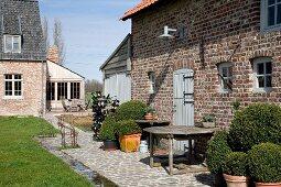 Terrasse mit Buchsbäumen in Töpfen vor altem englischen Landhaus