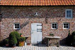 Renovierter Backsteinbau mit weisser Gattertür und Buchsbäume in Töpfen auf der Terrasse