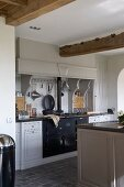 weiße Landhausküche mit schwarzem, eingebautem Retro-Ofen