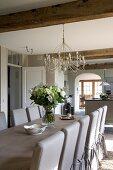 Festliche Tafel mit Blumenstrauss im offenen Landhaus-Esszimmer mit anschliessender Küche