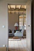 Blick durch die offene Tür ins Landhaus-Wohnzimmer auf einen Ohrenbacken-Sessel