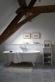 Freistehende Badewanne mit Klauenfüssen unter offener Dachkonstruktion
