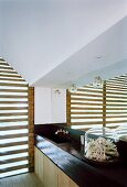 Badezimmer mit Holzlamellen vor dem Fenster