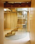 Wooden spiral staircase with curved glass wall