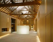 Designer-style, open-plan room in converted house with view of rustic roof timbers
