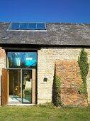 Renovated farmhouse with stone facade and open door