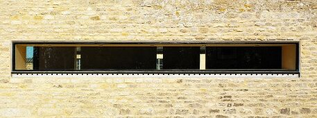 Narrow, horizontal window slit in stone facade